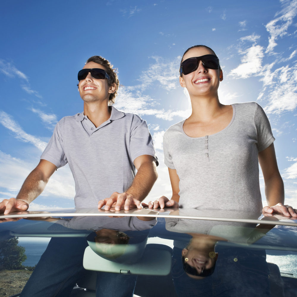 A young man and woman in sunglasses are standing out the top opening of their car.  Vertical shot.